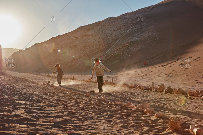 Boy and his brother pulling toy trucks along desert path, Atacama, Chile