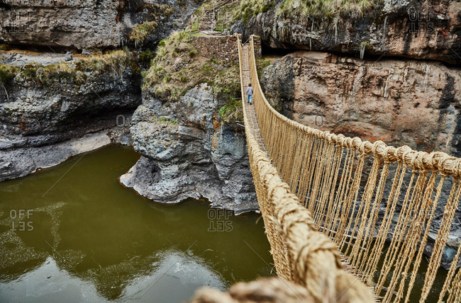Rear view of boy crossing Inca rope bridge, Huinchiri, Cusco, Peru