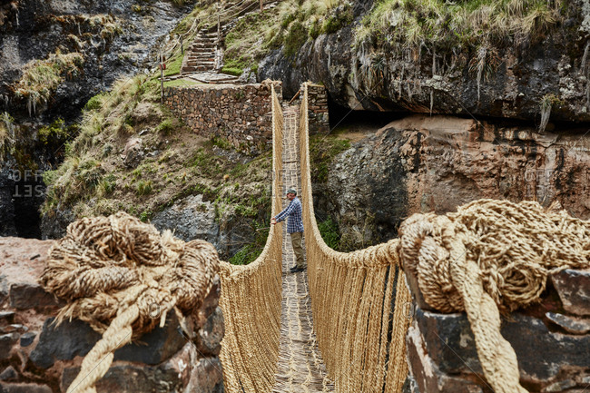 Male tourist looking out from Inca rope bridge, Huinchiri, Cusco, Peru
