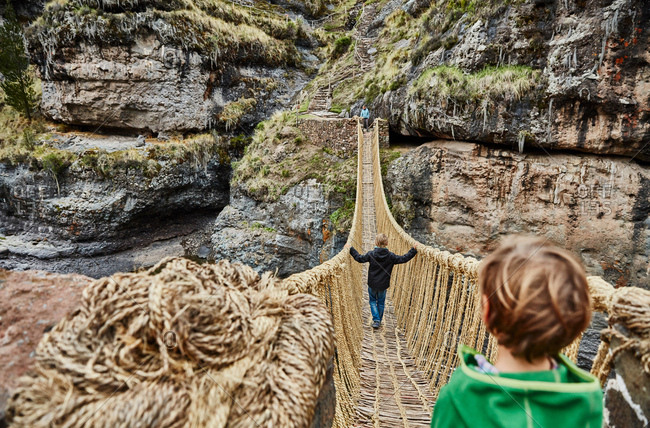Over shoulder view of boy, brother and mother crossing Inca rope bridge, Huinchiri, Cusco, Peru
