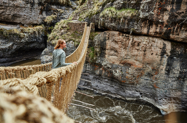 Female tourist looking out from Inca rope bridge, Huinchiri, Cusco, Peru