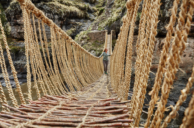 Female tourist crossing Inca rope bridge, Huinchiri, Cusco, Peru