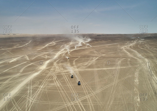 Landscape view of off road vehicles crossing dusty desert, Ica, Peru