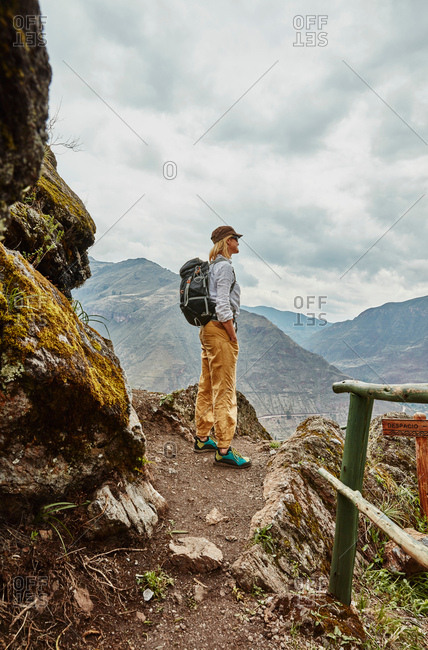 Female hiker looking out at distant mountains, Pisac, Cusco, Peru