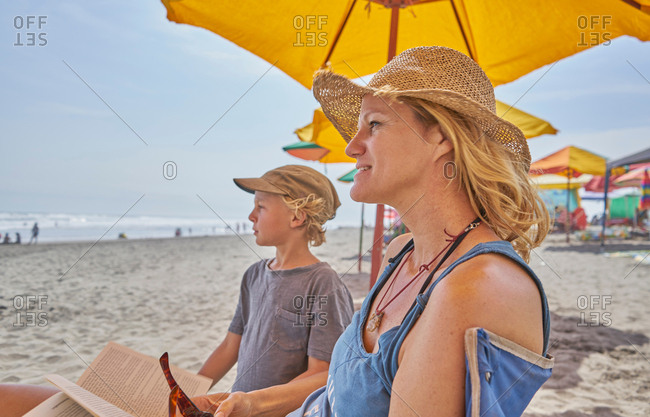 Mature woman and son relaxing on beach, Camana, Arequipa, Peru