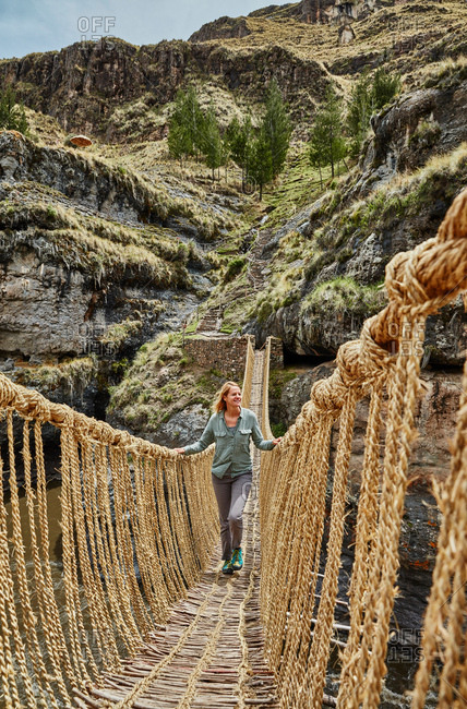 Mature woman crossing Inca rope bridge, Huinchiri, Cusco, Peru