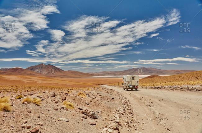 Recreational vehicle moving across landscape, rear view, Chalviri, Oruro, Bolivia, South America