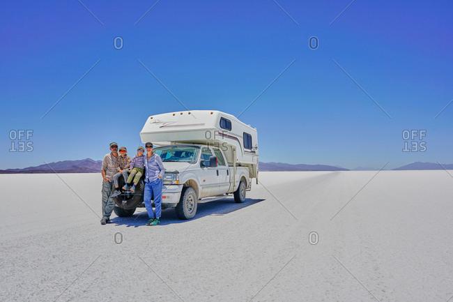 Portrait of family, standing in front of parked recreational vehicle, Salar de Uyuni, Uyuni, Oruro, Bolivia, South America