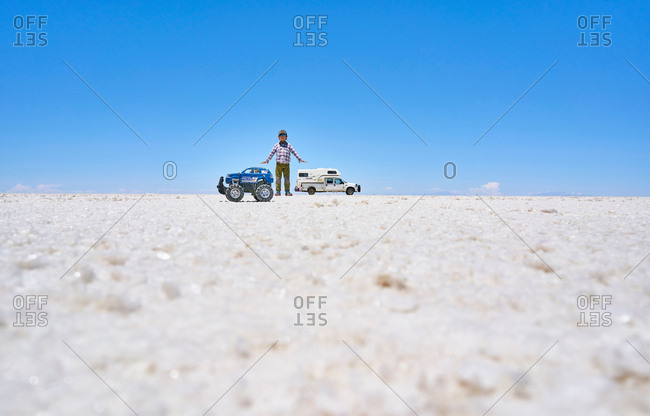 False perspective image of boy and toy truck on salt flats, standing taller than recreational vehicle in background, Salar de Uyuni, Uyuni, Oruro, Bolivia, South America