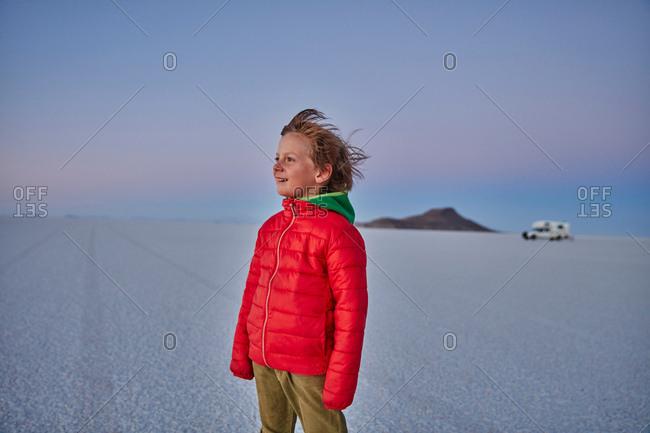 Young boy standing on salt flats, looking at view, recreational vehicle in background, Salar de Uyuni, Uyuni, Oruro, Bolivia, South America
