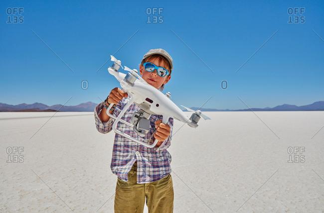 Portrait of boy on salt flats, holding drone, Salar de Uyuni, Uyuni, Oruro, Bolivia, South America