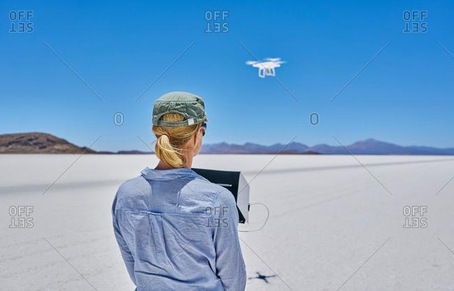 Woman on salt flats, flying drone, rear view, Salar de Uyuni, Uyuni, Oruro, Bolivia, South America