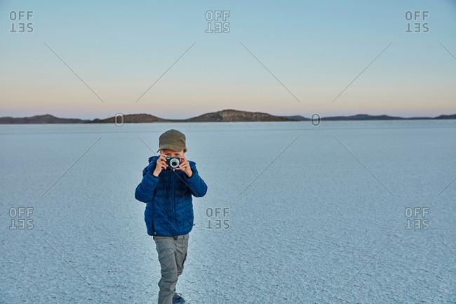 Young boy standing on salt flats, looking through camera, Salar de Uyuni, Uyuni, Oruro, Bolivia, South America