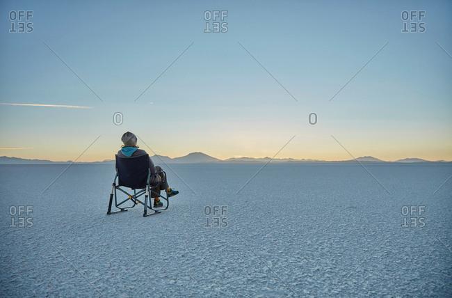 Woman sitting in camping chair, on salt flats, looking at view, Salar de Uyuni, Uyuni, Oruro, Bolivia, South America