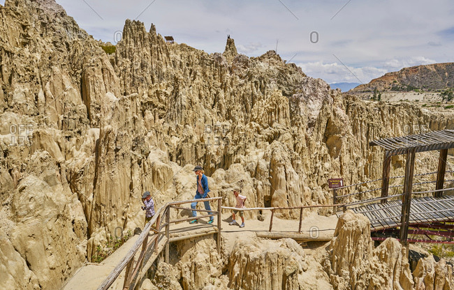 Mother and sons trekking along footpath, through rock formations, La Paz, Bolivia, South America