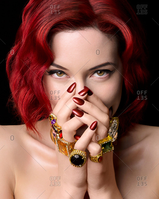 Portrait of young woman with red hair, hands covering face, wearing rings on all fingers