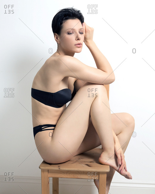 Studio shot of sultry young woman in bra and knickers sitting on stool