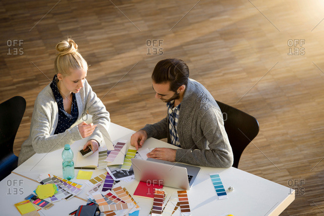 Male and female designer discussing color swatches on design studio table
