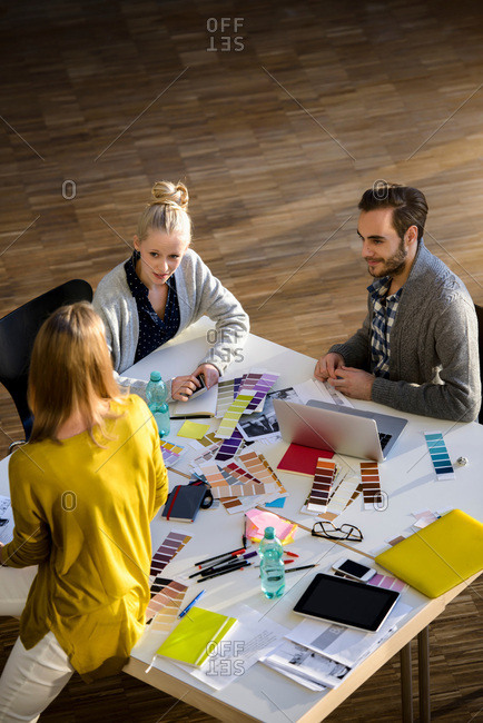 Male and female designers discussing color swatches on design studio table