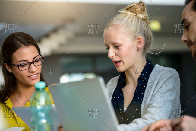 Male and female designers looking at laptops on design studio desk