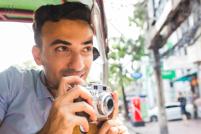 Young male tourist in auto rickshaw with camera, Bangkok, Thailand