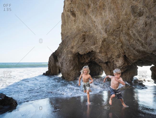 Brothers playing on El Matador Beach, Malibu, USA