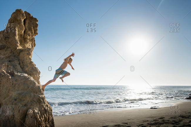 Boy jumping off rock, El Matador Beach, Malibu, USA