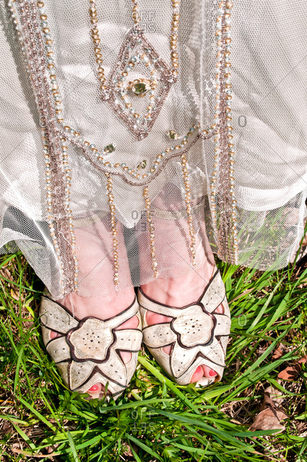 Bride wearing vintage wedding dress and shoes, close-up, low section