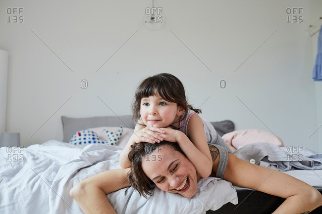 Mother and daughter lying on bed, daughter lying on mother's back