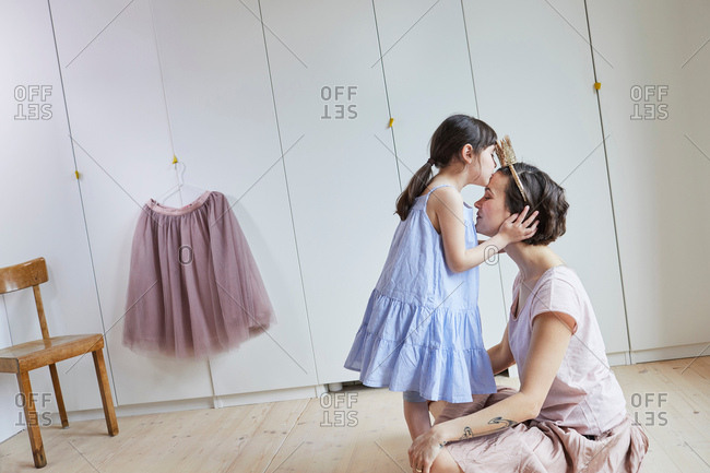 Mother and daughter in bedroom, face to face, daughter kissing mother on head