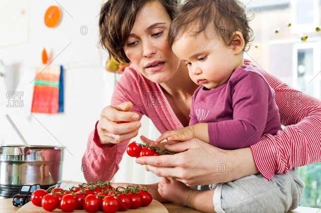 Mother and baby daughter in kitchen, sorting through tomatoes on kitchen counter