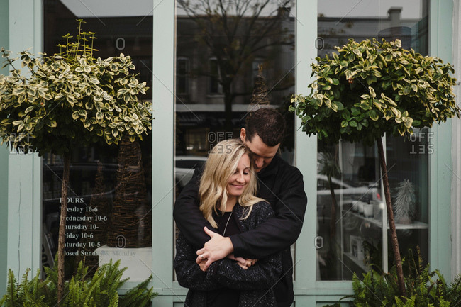 Portrait of mid adult couple in street, man hugging woman