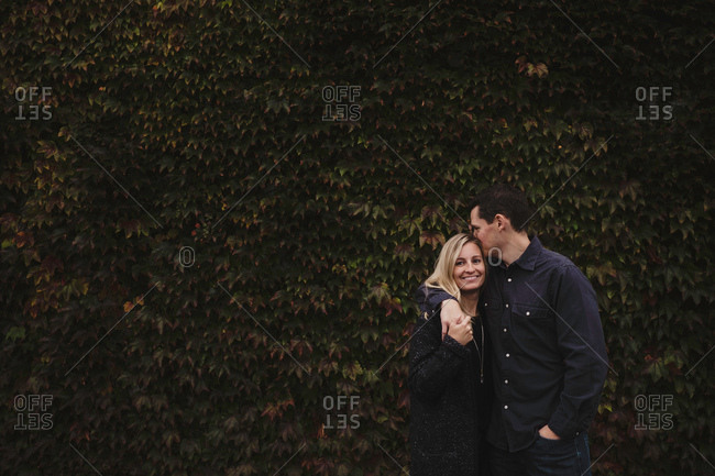 Portrait of mid adult couple, outdoors, hugging