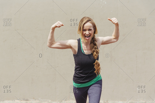 Cheerful woman in sportswear making face while flexing muscles against wall