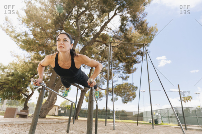Determined mid adult athlete exercising on parallel bars at park