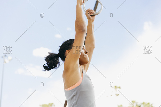 Side view of determined young woman exercising on gymnastic rings against sky at park