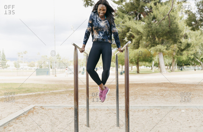 Full length of happy young athlete exercising on parallel bars at park