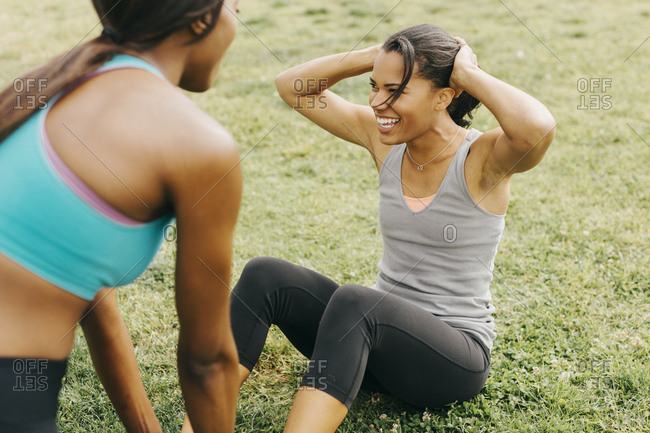 Friend assisting  woman in doing  crunches on grassy field at park