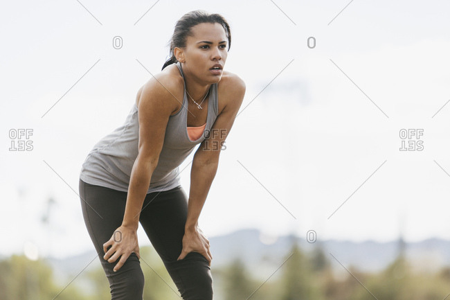 Tired young woman after workout standing at park against sky