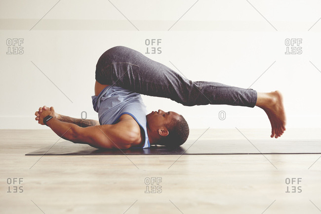 Young man practicing plow pose on exercise mat by wall at health club