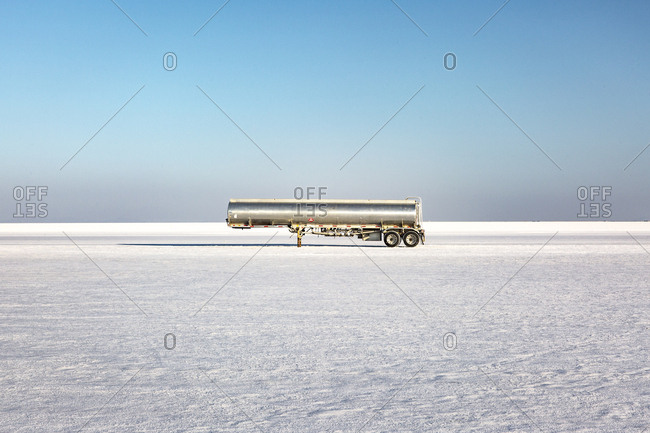 Mid distant view of tank trailer on salt flat against clear sky at Utah