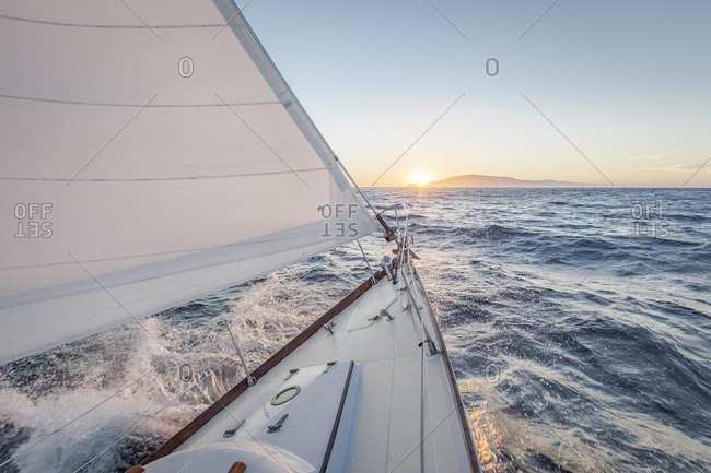 High angle view of boat splashing water while moving on sea against sky during sunset