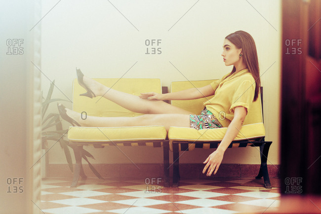 Young woman wearing shorts and high heels reclining on chairs