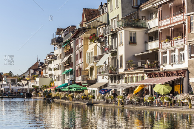 Thun, Switzerland - October 15, 2017: Row of houses with pavement cafes and restaurants at riverside of Aare