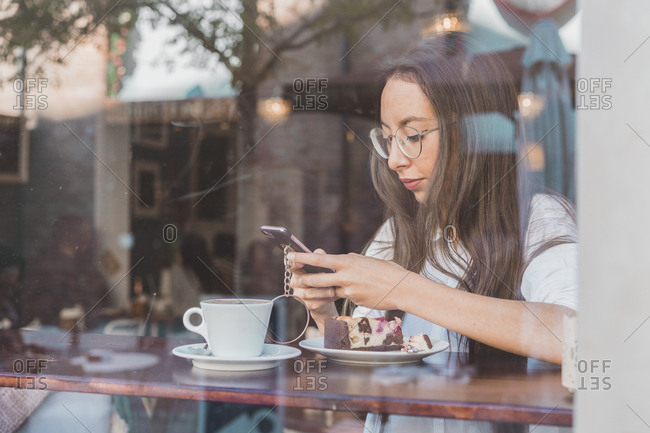 Woman with cake checking her cell phone in a cafe