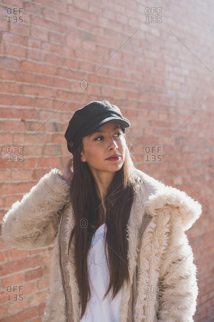 Stylish young woman in front of brick wall