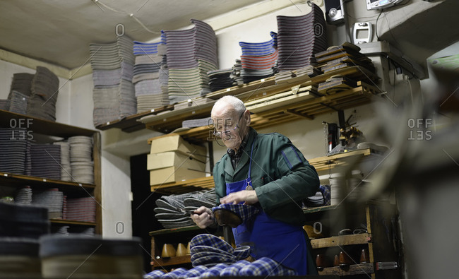 Senior shoemaker working on slippers in workshop