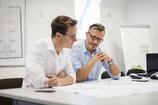 Two businessmen discussing plan on desk in office