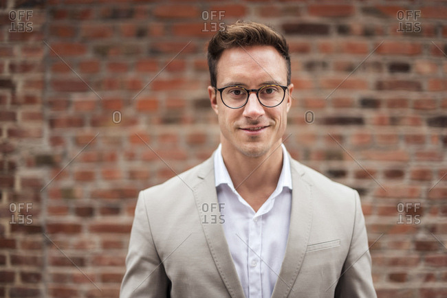 Portrait of smiling young businessman at brick wall