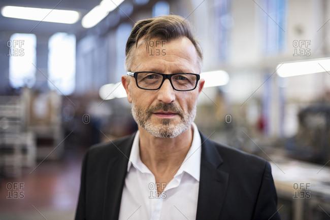 Portrait of confident mature businessman in factory